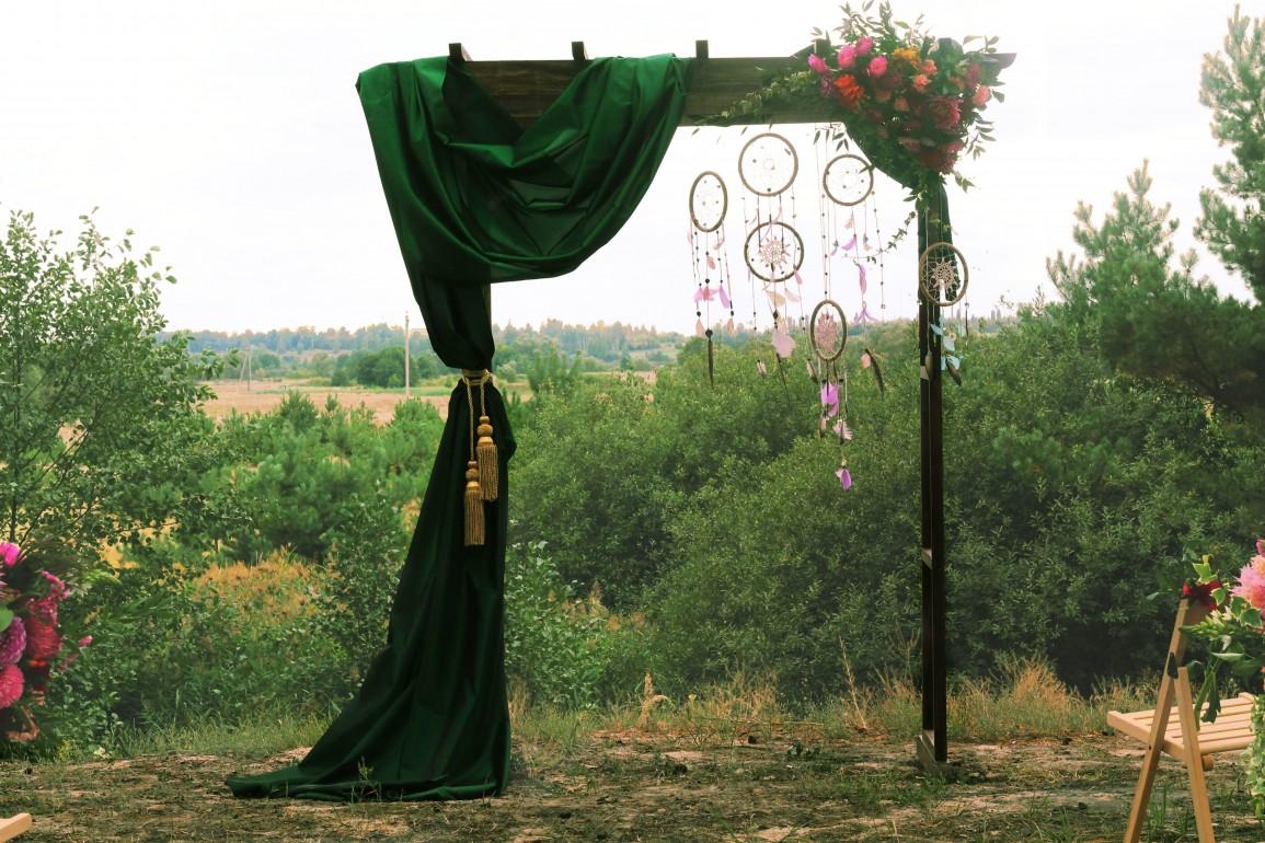 Удивительная арка украшенная тканью богатого изумрудного оттенка и гирляндой состоящей из ловцов снов.