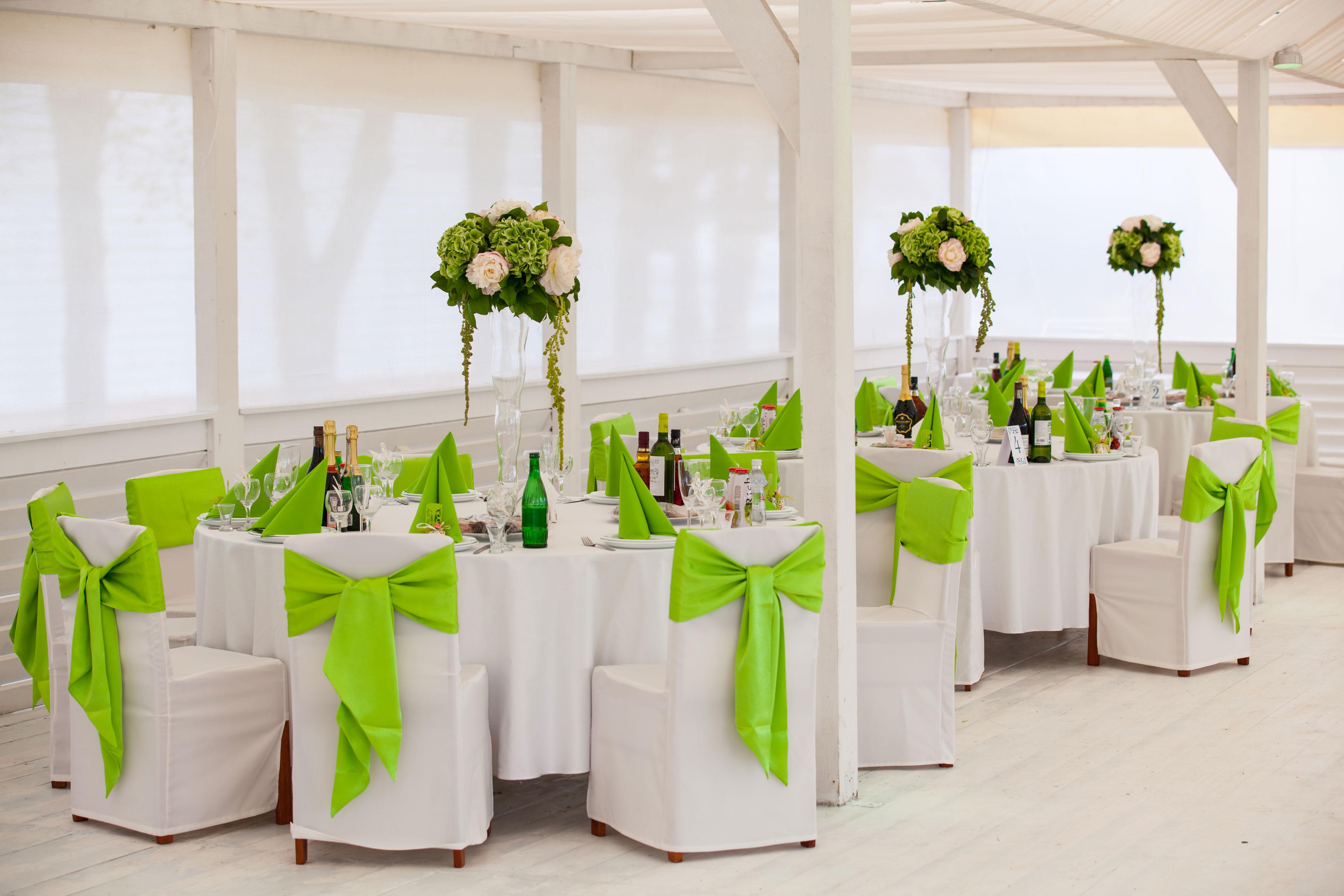 Декорирование стульев бантом зеленого цвета средней сложности создания.