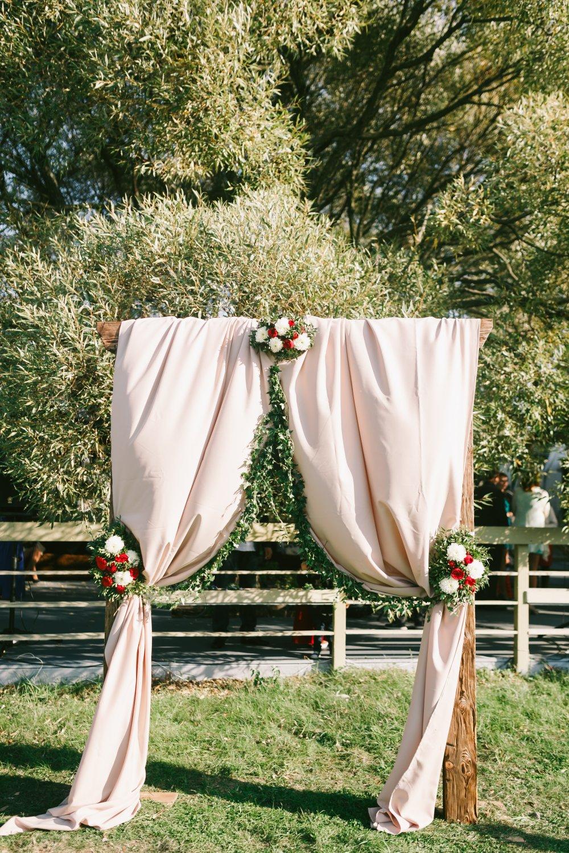 Свадебная арка украшенная цветами и тканью. Белая ткань придает арке более романтического внешнего вида.